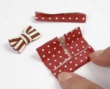Štvorček filcu prehnite na oboch stranách, zošite a previažte ďalším prešitým prúžkom filcu.